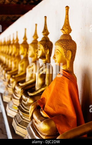 A line of gilded Buddha statues at That In Hang Temple, Savannakhet, Laos. - Stock Photo