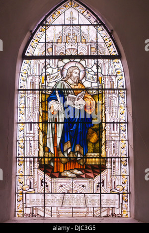 Stained glass window featuring St Luke in St Peter's church on Sark UK - Stock Photo