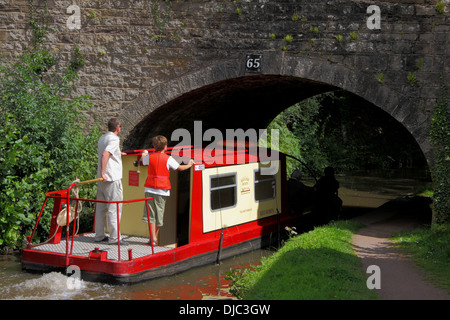 Narrowboat going under a bridge on the Monmouthshire and Brecon Canal, Powys,  Wales, UK - Stock Photo