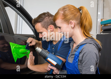 car wrapping professional wrapping car door handle in colorful foil or film using a squeegee - Stock Photo