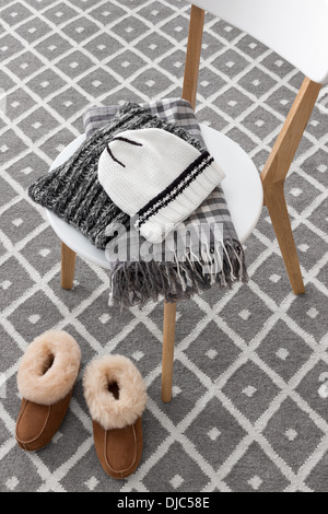 Warm slippers and winter clothes on a chair. - Stock Photo