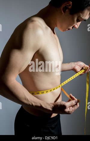 Shirtless athletic male measuring his waistline - Stock Photo