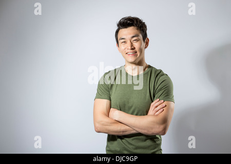 Athletic young male standing with arms folded - Stock Photo