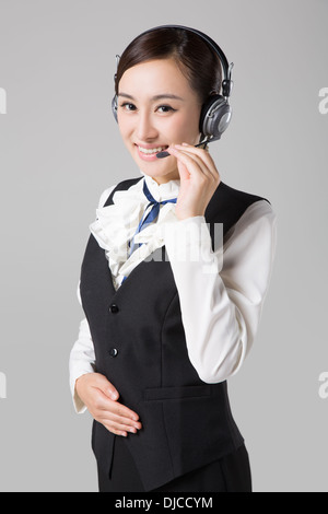 Young Eastern woman in uniform making telephone call - Stock Photo
