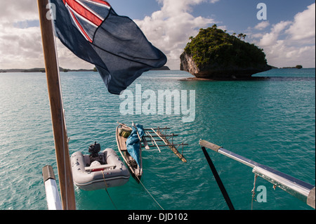 A traditional local sail boat, called a camakau, and a dinghy hanging off the back of a visiting yacht. Fulaga lagoon, - Stock Photo