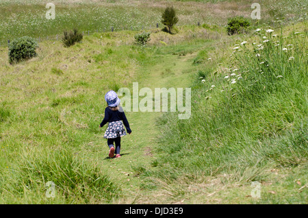 Little girl walks on a path lost in a rain forest. Travel concept ...