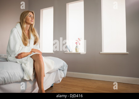 Smiling blonde wearing bathrobe sitting on bed - Stock Photo