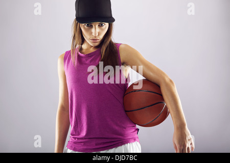 Female basketball player holding ball against grey background. Young woman holding basketball looking at camera - Stock Photo