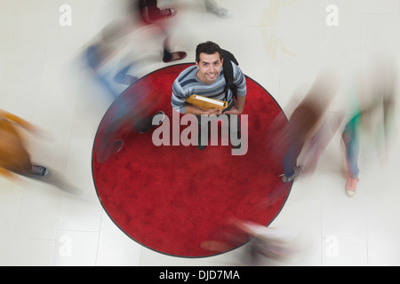 Happy student looking up at camera with others rushing around him - Stock Photo
