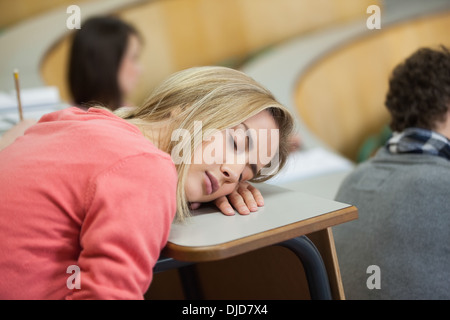 Blonde student sleeping in a lecture hall - Stock Photo