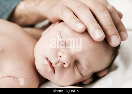Germany, Cologne, Mother touching head of newborn son - Stock Photo