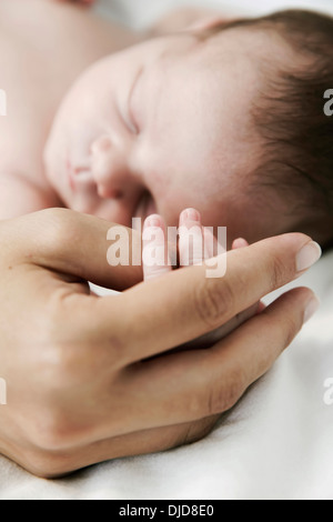 Mother holding hand of her sleeping newborn son - Stock Photo