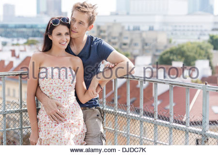 Woman standing at balcony railing overlooking ocean stock for Balcony overlooking city