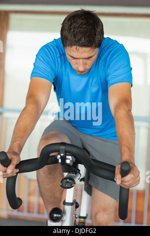 Man working out at spinning class in gym - Stock Photo