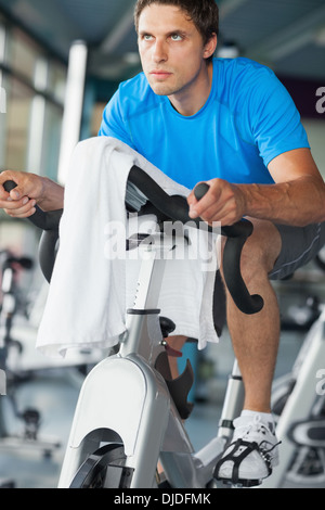 Determined man working out at spinning class - Stock Photo