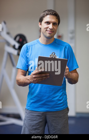 Portrait of a smiling trainer with clipboard in gym - Stock Photo