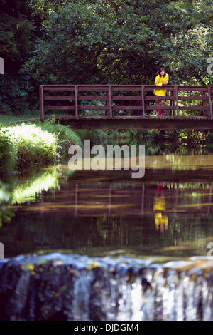 Woman on footbridge over lake and amid foliage - Stock Photo