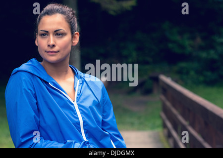 Thoughtful healthy young woman standing on footbridge - Stock Photo