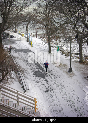 A runner in the snow near the Bayside Marina in Queens, New York - Stock Photo