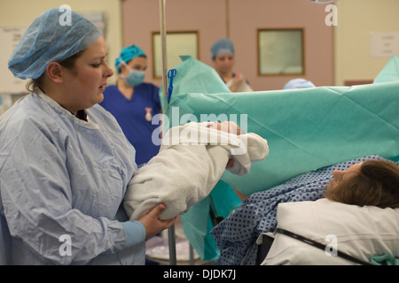 Newborn baby boy being checked by nurses in hospital maternity theatre on the Labour Ward at hospital, Kingston - Stock Photo