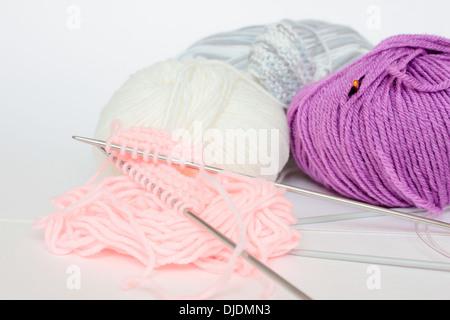 knitting 'knitting needles' yarn skein skeins wool woven purple pink white 'whote background' nobody - Stock Photo