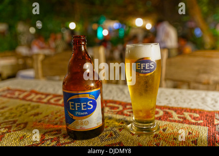 Efes Pilsen beer bottle and beer glass, Dalyan, Muğla Province, Turkish Riviera or Turquoise Coast, Aegean, Turkey - Stock Photo