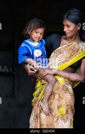 Happy smiling rural Indian mother and son in their house doorway. Andhra Pradesh, India - Stock Photo