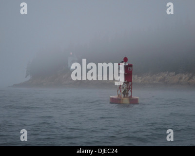 A red and white buoy and the Bass Harbor lighthouse in the fog along the coast of Maine USA - Stock Photo