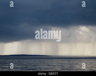 Visible rain falling from dark clouds over the ocean. - Stock Photo