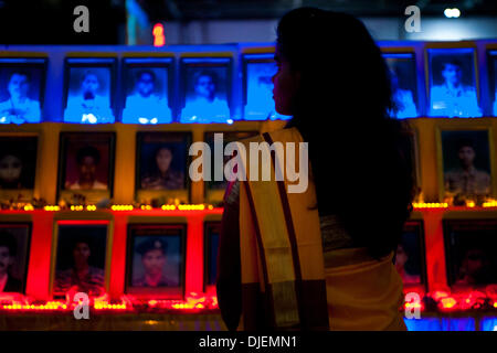 "London, UK. 27th November 2013.  A woman stands in front of pictures of the ""Maaveerar"", the Fallen Heroes of Tamil - Stock Photo"