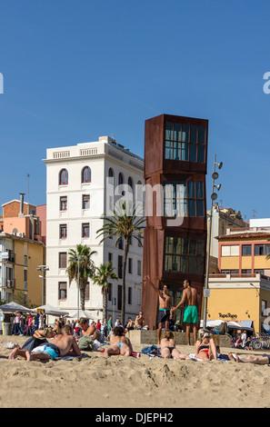 Barceloneta beach, Sculpture by Rebecca Horn, girls sunbathing, Barcelona, Spain - Stock Photo
