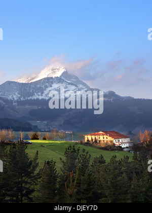 typical basque country house in Aramaio valley surrounding by mountains - Stock Photo