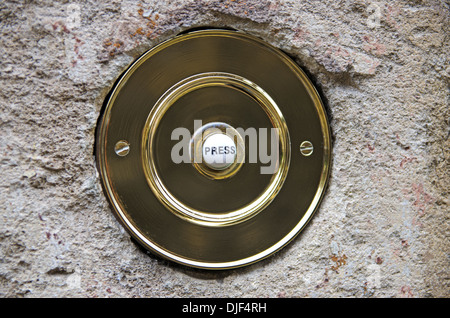 Circular brass door bell on a weathered stone wall - Stock Photo