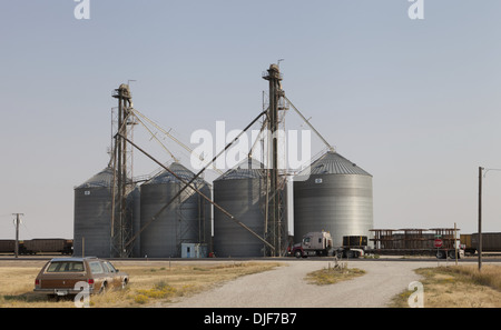 Abandoned car and a Freightliner semi highway truck parked beside grain silos in Moccasin, Montana - Stock Photo