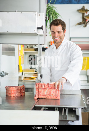Butcher Cutting Meat On Bandsaw - Stock Photo