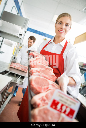 Happy Butcher Showing Meat Tray In Store - Stock Photo