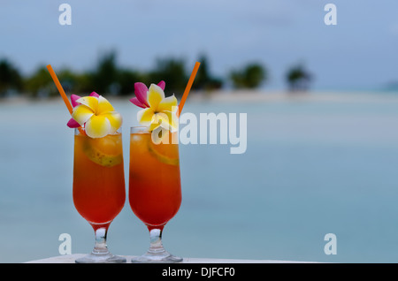 Tropical cocktails served outdoor on Pacific Island resort with turquoise water in the background. - Stock Photo
