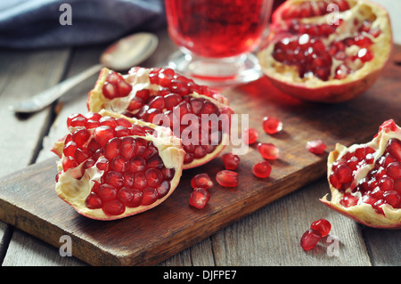 Ripe pomegranate fruit and glass of juice on wooden background - Stock Photo