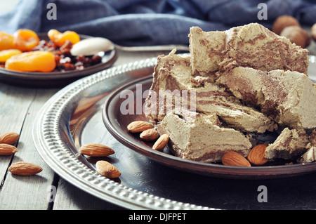 Halva with almonds and raisins on plate closeup - Stock Photo