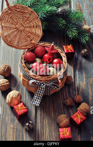 Christmas decorations in wicker basket and fir tree on wooden background - Stock Photo