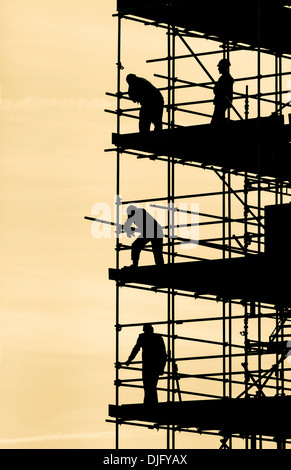 Scaffolders working on block of flats silhouetted againt bright Autumnal sky - Stock Photo