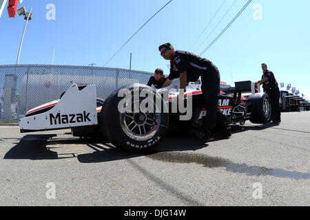 Team Penske crew members navigate the Honda of Ryan Briscoe back to the garage stall on Friday morning for the Camping - Stock Photo