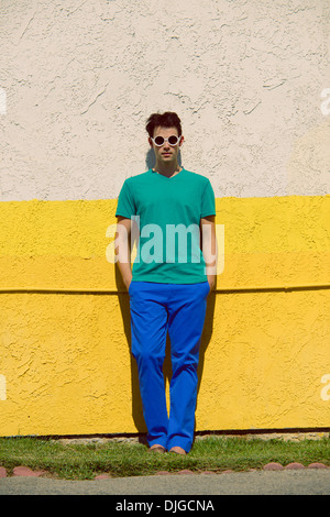 A young man with round sunglasses,standing against yellow wall,wears a green shirt and blue pants, a color block - Stock Photo