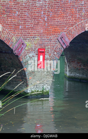 A Royal Mail post box placed in a completely inaccessible position on a river bridge pier surrounded by water. - Stock Photo