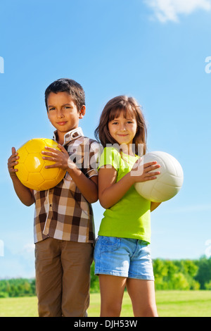 Couple of kids 6 years old, boy and girl holding balls in the park - Stock Photo