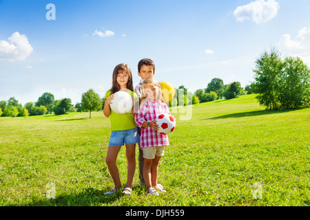 Three happy kids, boy and girls standing in the sunny summer park holding sport balls - Stock Photo