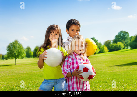 Team of three happy kids, boy and girls standing in the sunny summer park holding sport balls - Stock Photo