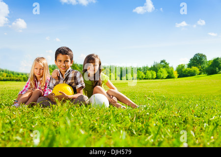 Three happy kids, boy and girls sitting in the sunny summer park holding sport balls - Stock Photo