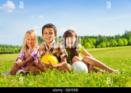 Portrait of three happy kids, boy and girls sitting in the sunny summer park holding sport balls - Stock Photo