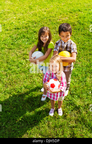 Three happy kids, boy and girls standing in the sunny summer park holding sport balls, view from top - Stock Photo